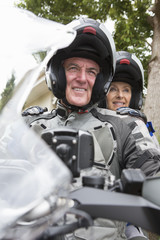 Portrait of smiling senior couple wearing helmets on motorcycle
