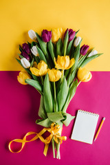 top view of spring tulips with notepad and pencil for international womens day