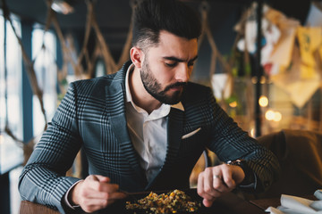 Rich handsome man checking time on his watch while eating a meal in a fancy restaurant.