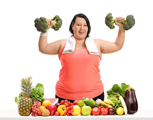 Overweight woman exercising with broccoli dumbbells behind a table with fruit and vegetables