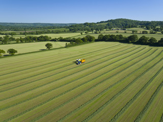 Aerial view of forage harvester cutting grass silage crop in field