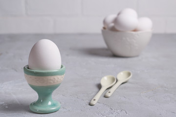 White  chicken  egg in ceramic stand and eggs in white  bowl . On a gray concrete background.