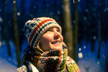 Portrait of smiling woman looking up in knitted cap in evening winter forest