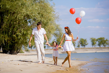 Mom, dad and daughter walking on the beach