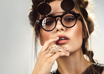 Beautiful fashion woman with creative make-up and hairstyle wearing glasses and jewelry. The beauty of the face. Photos shot in the studio. Wall mural