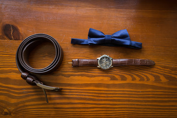 Groom's accessories: blue necktie, leather belt, and a watch