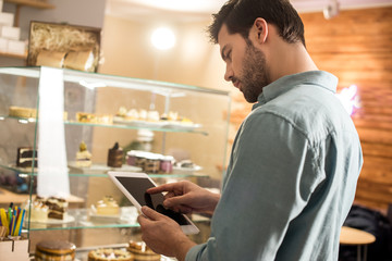 side view of barista using tablet at work in coffee shop