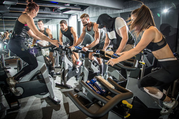 Group of fitness people doing cardio workout on indoor cycling bikes at gym.