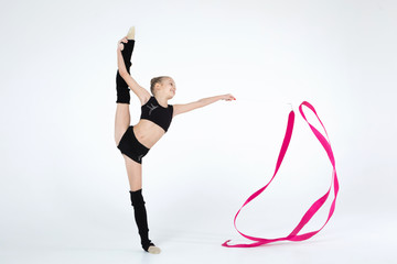 Rhythmic gymnastics caucasian blonde girl in black suite performing athelete exercises with pink ribbon handling abilities showing flexibility and acrobat balance on white background isolated