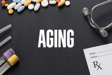 AGING written on black background with medication
