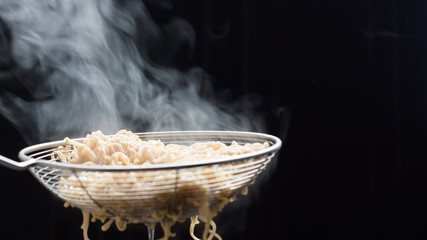 Noodles in a basket that just boiled from hot soup pot with steam selective focus,soft focus