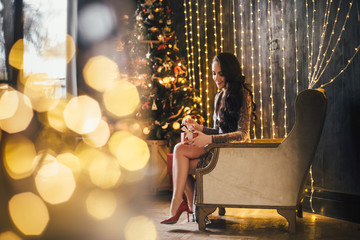 The beautiful girl sitting on the chair and keeping a present