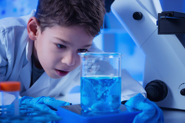Schoolboy using lab equipment, laboratory education concept