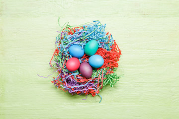 Photo of multi-colored Easter eggs on green wooden background with blank space