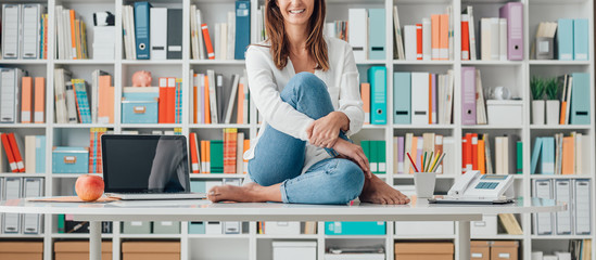 Smiling woman sitting on the top of the desk