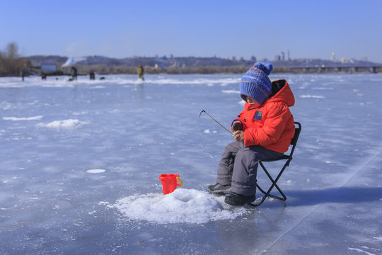 a little boy is fishing on a frozen lake