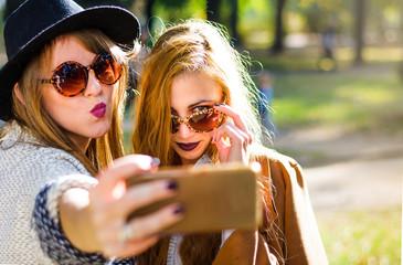 Girlfriends taking a selfie in the park