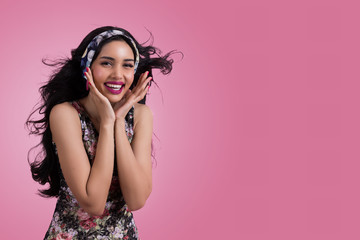 Beautiful young woman are smiling happily on a pink background.