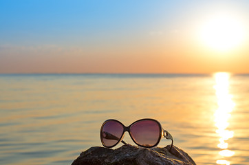 Fotomurais - women's sunglasses on the stone, against the background of the sea and the sun