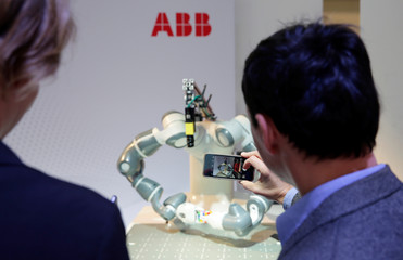 Man takes pictures of Humanoid robot YuMi ahead of a news conference by Swiss power technology and automation group ABB presenting the company's full year results, in Zurich