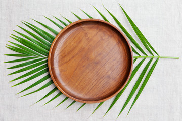 Wooden plate with palm leaf. Copy space. Top view.
