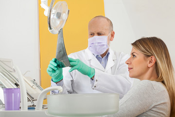 Dentist and patient looking to dental x-ray