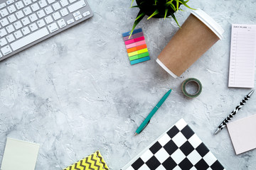 Creative mess on student's desk. Keyboard, notebook, stationery, coffee cup, plant on grey background top view copy space