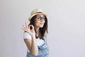 portrait of a young beautiful woman with modern glasses and hat. White background. Millennial. Hipster and lifestyle.Making the ok sign with hands