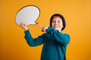 Cheerful little redhead boy holding speech bubble.