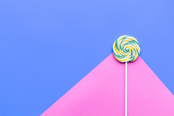 Color lollipop swirl on blue and pink pastel background top view copy space