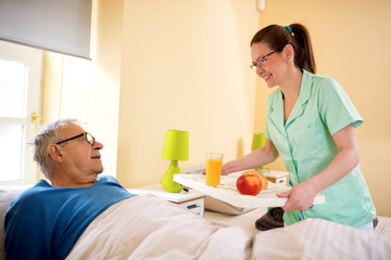 Young smiling nurse brings breakfast to senior patient