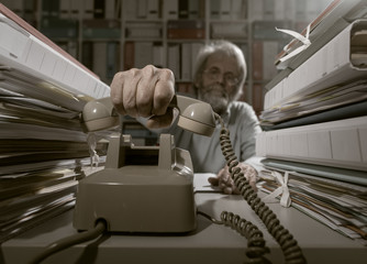 Senior office worker answering calls