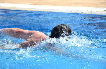 Detail of a Caucasian man swimming crawl stroke in an outdoor pool.