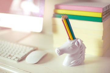 workspace front view computer keyboard mouse and unicorn pencil holder, rainbow colour pencils and books on background, rainbow colours