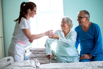 Nursing home, young careful nurse brings water to old woman