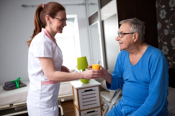 Nurse at nursing home brings orange juice to old patients