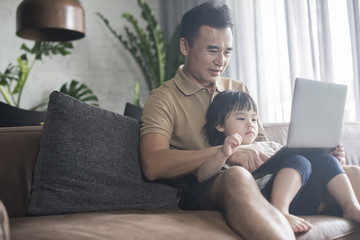 Happy Asian father looking at the computer with daughter at home.