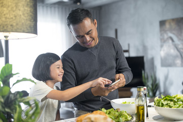 Happy Asian father spending time with daughter in the kitchen.
