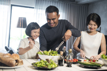 Happy Asian family preparing food in the kitchen.