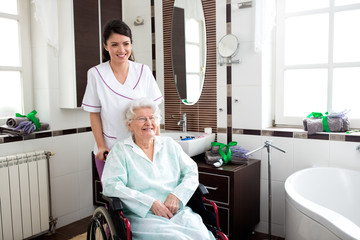 Nurse helping to old woman in wheelchair