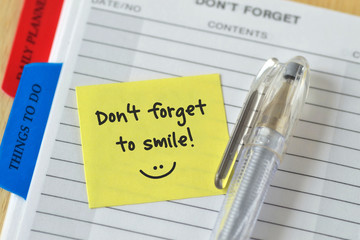 Text don't forget to smile written on a sticky note over an agenda background