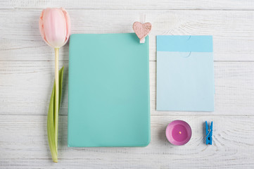 Mint notebook, tulips and lit candle