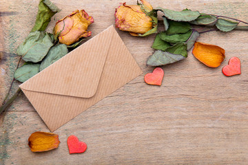 Dried orange roses and envelope on wooden background, copy space