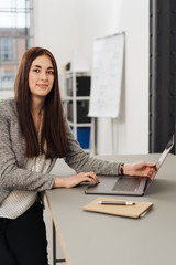 Young woman sitting at desk with laptop