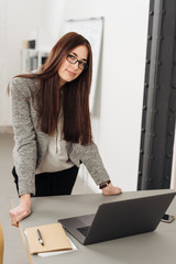 Young woman standing over computer in office