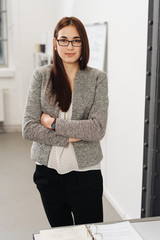 Confident young businesswoman with folded arms