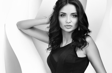 Black and white portrait of young beautiful woman have wavy walls. Beautiful dark hair, makeup