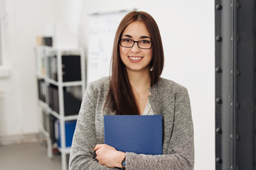 Young smiling woman holding files in office