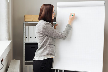 Young woman writing on flip chart in office