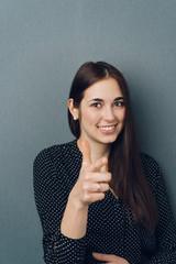 Fun smiling woman pointing at the camera
